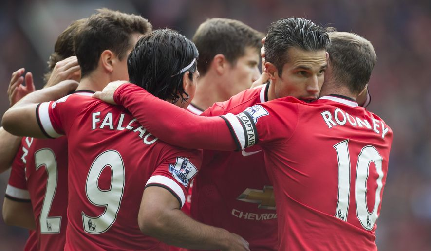 Manchester United's Robin van Persie, second right, celebrates with teammates after scoring against West Ham United during their English Premier League soccer match at Old Trafford Stadium, Manchester, England, Saturday Sept. 27, 2014. (AP Photo/Jon Super)