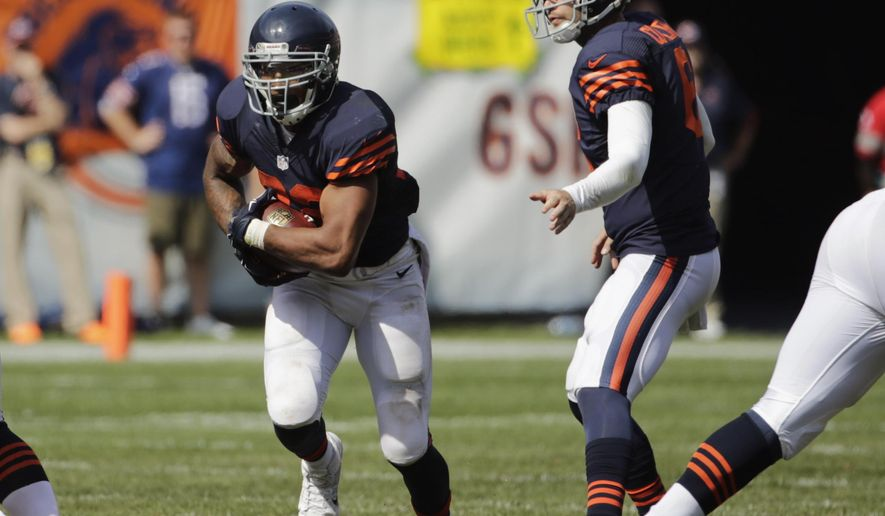 Chicago Bears running back Matt Forte (22) runs after taking a handoff from quarterback Jay Cutler (6) in the first half of an NFL football game against the Green Bay PackersSunday, Sept. 28, 2014, in Chicago. The Packers won 38-17. (AP Photo/Charles Rex Arbogast)
