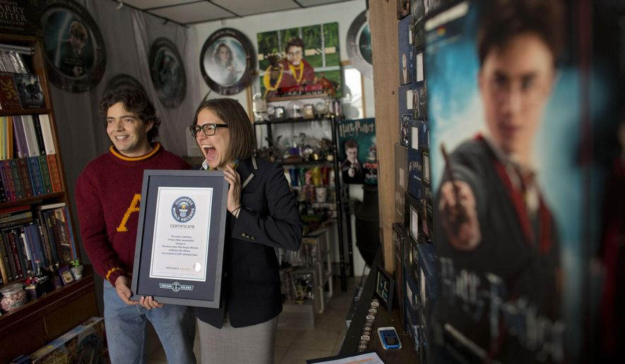 Johanna Hessling of Guinness World Records, right, presents Menahem Asher Silva Vargas, a 37 year old lawyer, with a certificate recognizing him as the title holder for the largest collection of Harry Potter memorabilia, at his home in Mexico City, Monday, Sept. 29, 2014. Silva's 14 year old collection consists of more than 3000 individual items, including figurines, trading cards, wands, clothing, and accessories.(AP Photo/Rebecca Blackwell)