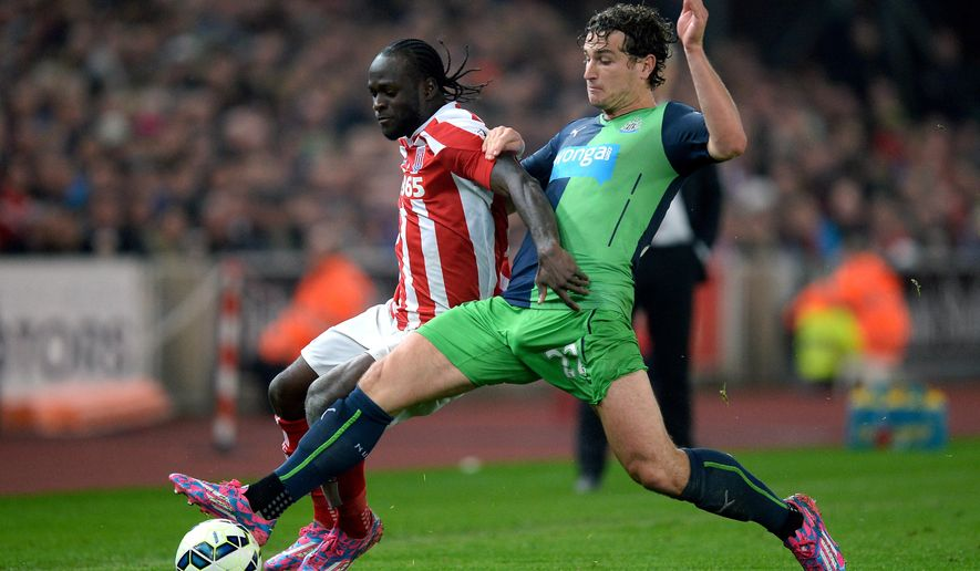 Stoke City's Victor Moses, left, battles for the ball with Newcastle United's Daryl Janmaat, during the English Premier League soccer match between Stoke City and Newcastle United, at the Britannia Stadium, in Stoke on Trent, England, Monday Sept. 29, 2014. (AP Photo/PA, Martin Rickett) UNITED KINGDOM OUT
