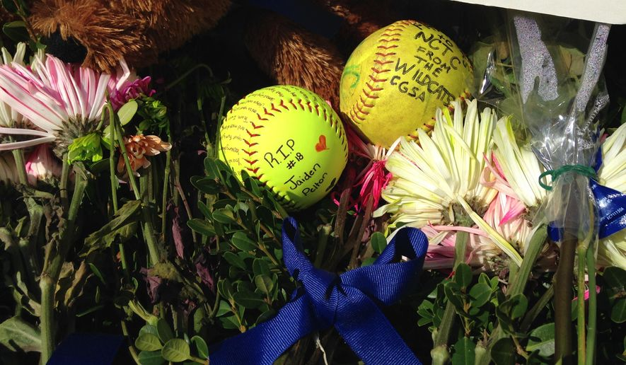 Students at North Central Texas College left flowers, teddy bears and softballs inscribed with prayers outside an administration building on campus in Gainesville, Texas, on Monday, Sept. 29, 2014. Four softball players were killed Friday night in a highway crash still under investigation in Oklahoma. (AP Photo/Emily Schmall)