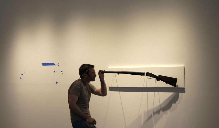 "In this Friday, Sept. 26, 2014 photo, artist Adam Mysock installs his artwork, titled ""Looking Down The Barrel of a Gun (The Last Judgement),"" for the upcoming exhibit ""Guns in the Hands of Artists,"" at the Jonathan Ferrara Gallery in New Orleans.  (AP Photo/Gerald Herbert)"