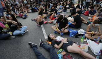 Pro-democracy protesters take afternoon naps on the streets in Hong Kong Monday, Sept. 29, 2014. Pro-democracy protesters expanded their rallies throughout Hong Kong on Monday, defying calls to disperse in a major pushback against Beijing's decision to limit democratic reforms in the Asian financial hub. (AP Photo/Wong Maye-E)
