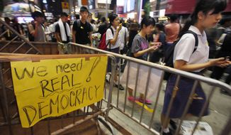 "Students gather to attend a ""sit-in"" to block main roads of a popular fashion district in Hong Kong, Monday, Sept. 29, 2014. Pro-democracy protesters expanded their rallies throughout Hong Kong on Monday, defying calls to disperse in a major pushback against Beijing's decision to limit democratic reforms in the Asian financial hub. (AP Photo/Wally Santana)"