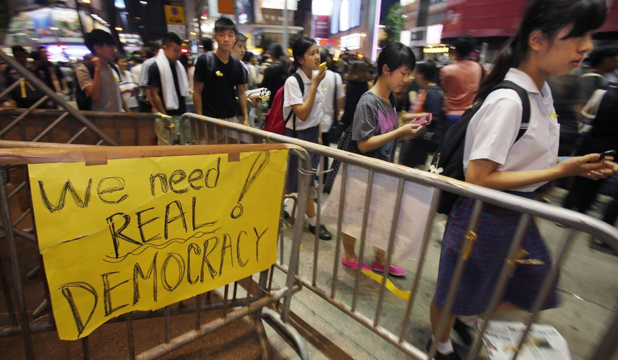 """Students gather to attend a """"sit-in"""" to block main roads of a popular fashion district in Hong Kong, Monday, Sept. 29, 2014. Pro-democracy protesters expanded their rallies throughout Hong Kong on Monday, defying calls to disperse in a major pushback against Beijing's decision to limit democratic reforms in the Asian financial hub. (AP Photo/Wally Santana)"""