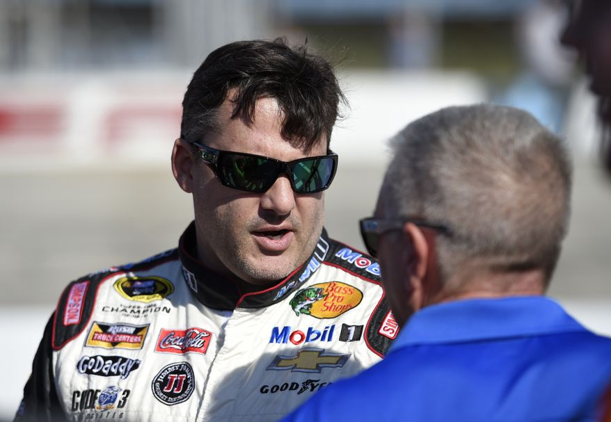 Tony Stewart, left, talks on pit road before qualifying for the NASCAR Sprint Cup series auto race, Friday, Sept. 26, 2014, at Dover International Speedway in Dover, Del. (AP Photo/Nick Wass)