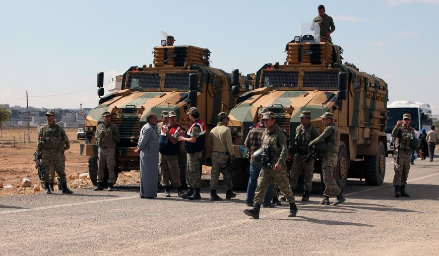 Turkish soldiers standby as Turkish Kurds gather nearby to express their solidarity with Kurdish fighters in Kobani, Syria, at the Turkey-Syria border near Suruc, Turkey, Monday, Sept. 29, 2014. U.S.-led coalition air raids targeted towns and villages in northern and eastern Syria controlled by the Islamic State group, including one strike that hit a grain silo and reportedly killed civilians, activists said Monday.(AP Photo/Burhan Ozbilici)
