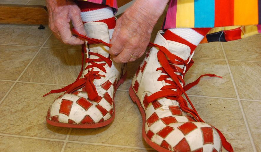 """In this March 29, 2012, file photo, Floyd """"Creeky"""" Creekmore ties his oversized shoes while getting dressed before a visit with children at a circus in Billings, Mont. (AP PhotoMatthew Brown, File)"""