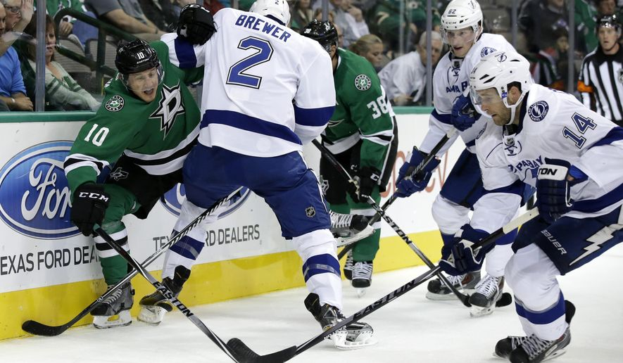 Dallas Stars' Shawn Horcoff (10) fights off a block by Tampa Bay Lightning's Eric Brewer (2) as Horcoff challenges right wing Brett Connolly (14) for control of the puck during the first period of a preseason NHL hockey game, Tuesday, Sept. 30, 2014, in Dallas. Stars' Vernon Fiddler (38) and Lightning's Andrej Sustr (62), of the Czech Republic, watch the play from the rear. (AP Photo/Tony Gutierrez)