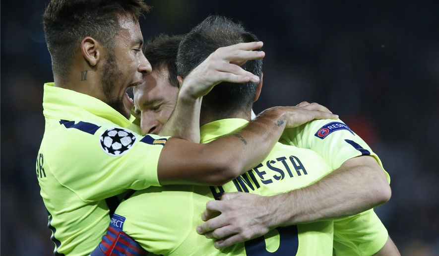 Barcelona's Lionel Messi, partially hidden by teammates, is congratulated by Neymar, left, and Barcelona's Andres Iniesta, right, as they celebrate his sides's first goal during the Champions League Group F soccer match between Paris Saint German and Barcelona at Parc des Princes stadium in Paris, France, Tuesday, Sept. 30, 2014. (AP Photo/Michel Euler)