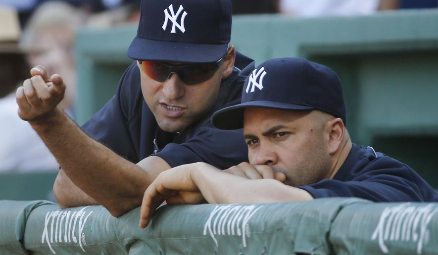 New York Yankees designated hitter Derek Jeter, left, gestures as he speaks to Carlos Beltran in the dugout during the Yankees' baseball game against the Boston Red Sox on Sunday, Sept. 28, 2014, in Boston. It is the last baseball game of Jeter's career. (AP Photo/Elise Amendola)