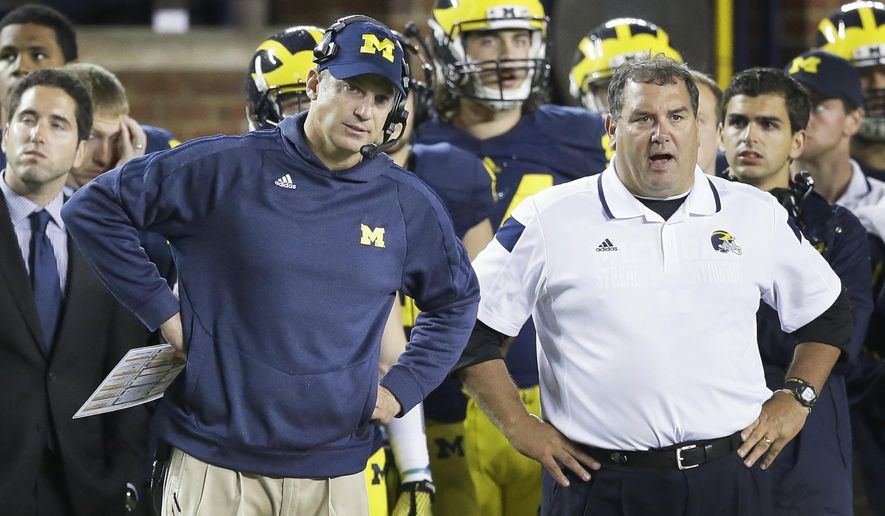 FILE - In this Sept. 20, 2014, file photo, Michigan offensive coordinator Doug Nussmeier, left, and head coach Brady Hoke watch from the sidelines during the closing minutes of their 26-10 loss to Utah during the second half of their NCAA college football game in Ann Arbor, Mich. Early Tuesday, Sept. 30, 2014, roughly 12 hours after embattled Michigan coach Brady Hoke said he'd been given no indication that quarterback Shane Morris had been diagnosed with a concussion, athletic director Dave Brandon revealed in a post-midnight statement that the sophomore did appear to have sustained one.  (AP Photo/Carlos Osorio, File)