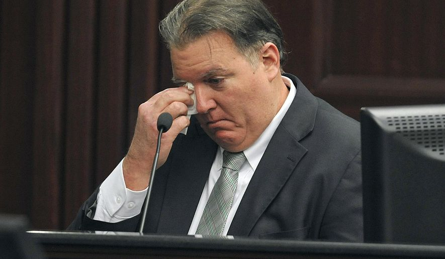 Michael Dunn wipes a tear as he testifies during his retrial at the Duval County Courthouse, Tuesday, Sept. 30, 2014, in Jacksonville, Fla. Dunn is being retried on murder charges for the shooting death of 17-year old Jordan Davis in a dispute over loud music at a Jacksonville gas station in November of 2012. Dunn was found guilty of three counts of attempted murder and one count of shooting or throwing a deadly missile during his previous trial, but the jury was deadlocked on the murder charge. (AP Photo/The Florida Times-Union, Bruce Lipsky, Pool)