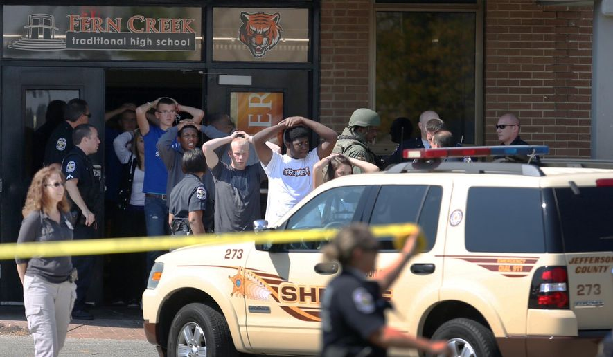 Students put their hands on their heads as they are lead out of Fern Creek High School in Louisville, Ky. on Tuesday, Sept. 30 2014 after a shooting. Officials said a student was injured and one person was being sought in connection with the incident. (AP Photo/The Courier-Journal, Scott Utterback)