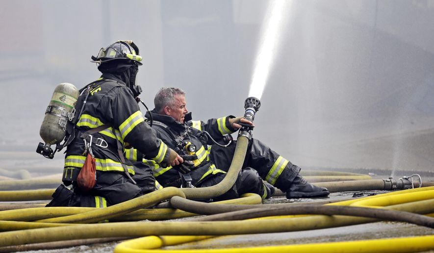 A firefighter briefly goes without his helmet as he prepares to put on a mask while hosing down a building on fire Tuesday, Sept. 30, 2014, in Seattle's Fremont neighborhood. No injuries were reported in the fire, which sent flames bursting through the roof of the building and created a large plume of smoke visible from downtown. (AP Photo/Elaine Thompson)