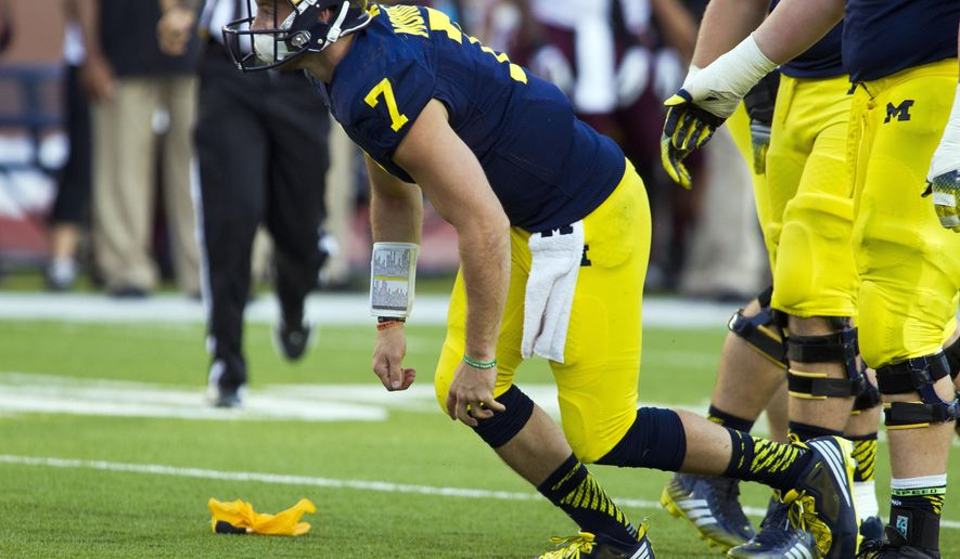 In this Sept. 27, 2014, photo, Michigan quarterback Shane Morris gets up from the field after taking a hit in the fourth quarter of an NCAA college football game against Michigan in Ann Arbor, Mich. Early Tuesday, Sept. 30, 2014, roughly 12 hours after embattled Michigan coach Brady Hoke said he'd been given no indication that Morris had been diagnosed with a concussion, athletic director Dave Brandon revealed in a post-midnight statement that the sophomore did appear to have sustained one.  (AP Photo/Tony Ding)