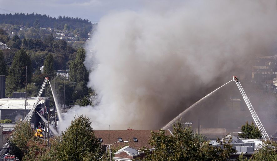 A plume of smoke dwarfs firefighters on ladders hosing down a building on fire Tuesday, Sept. 30, 2014, in Seattle's Fremont neighborhood. No injuries were reported in the fire, which sent flames bursting through the roof of the building and created a large plume of smoke visible from downtown. (AP Photo/Elaine Thompson)