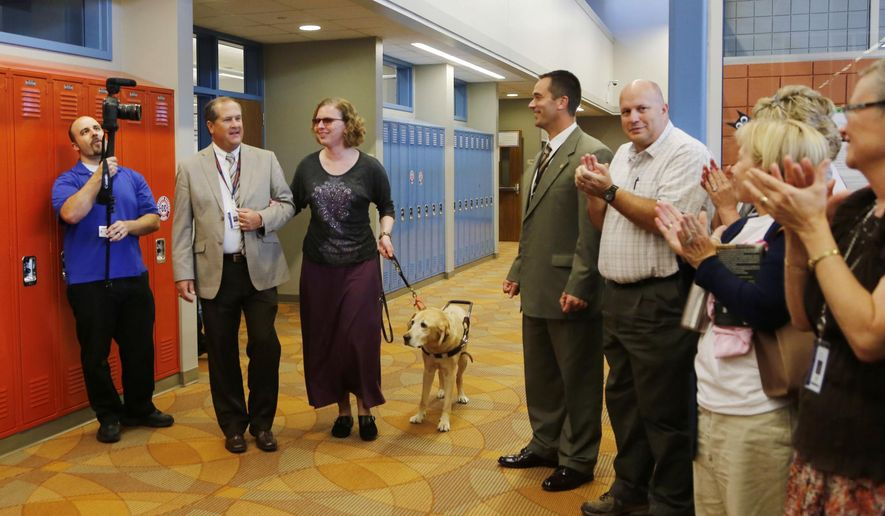 Assistant Principal Jerry Galema, second from left, escorts Kathy Nimmer and her service dog Elias from her classroom for a special ceremony Tuesday, Sept. 30, 2014, at Harrison High School in West Lafayette, Ind. Moments later, Superintendent of Public Instruction Glenda Ritz announced Nimmer as the Indiana Teacher of the Year. (AP Photo/Journal & Courier, John Terhune)