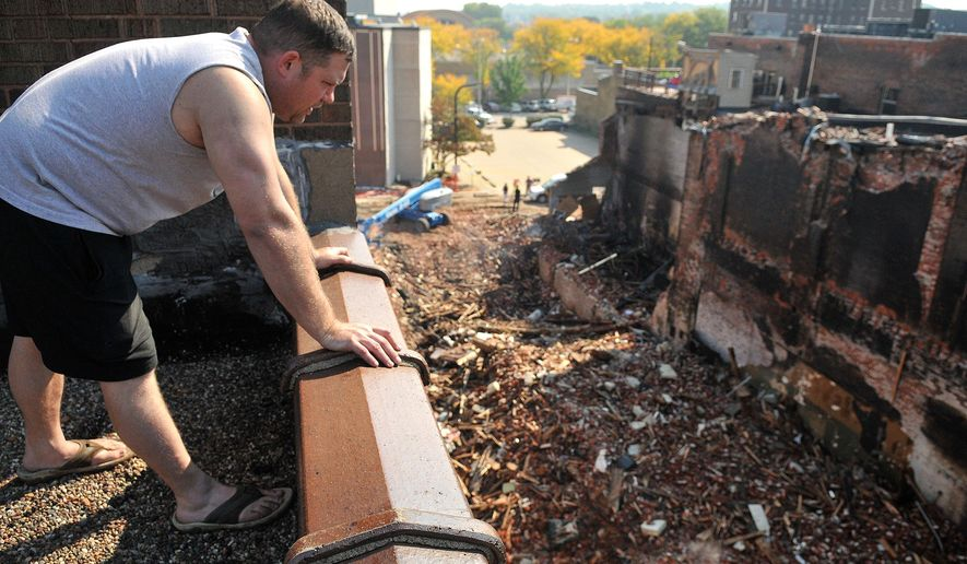 In this Monday Sept. 29, 2014 photo, smoke still rises from the rubble of a Saturday morning fire as John Boeh surveys fire damage from his rooftop vantage point in downtown Rock Island, Ill. Rock Island residents have started the recovery process after a weekend fire ripped through the heart of downtown, destroying or damaging eight buildings in the western Illinois city. (AP Photo/The Dispatch, Paul Colletti)  QUAD CITY TIMES OUT