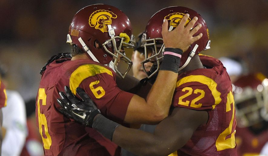 Southern California running back Justin Davis, right, is congratulated by quarterback Cody Kessler, left, as head coach Steve Sarkisian looks on after scoring a touchdown during the second half of an NCAA college football game, Saturday, Sept. 27, 2014, in Los Angeles.  USC won the game 35-10. (AP Photo/Mark J. Terrill)