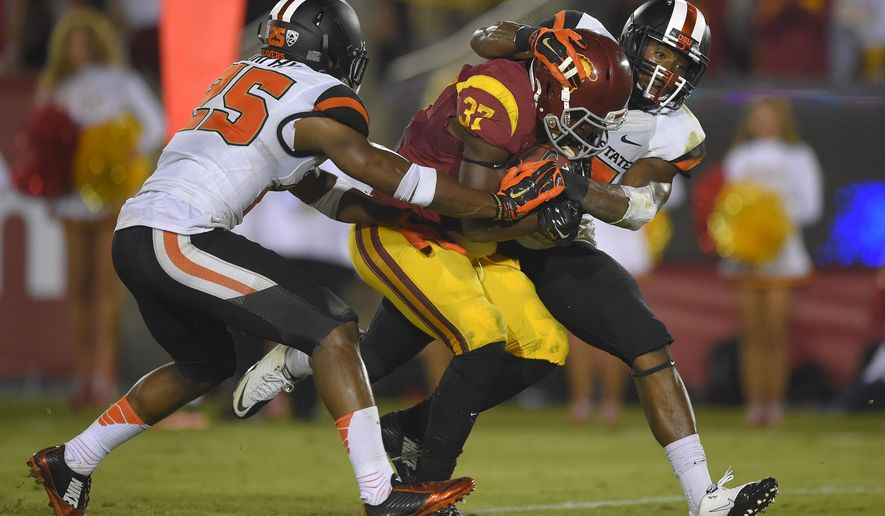 Southern California running back Javorius Allen, center, scores as Oregon State safety Ryan Murphy, left, and safety Cyril Noland-Lewis try to tackle him during the second half of an NCAA college football game, Saturday, Sept. 27, 2014, in Los Angeles.  USC won the game 35-10. (AP Photo/Mark J. Terrill)