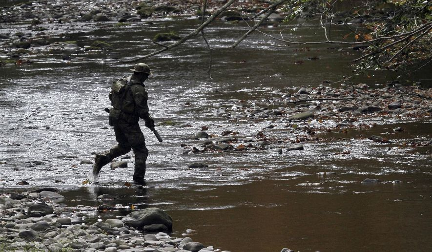 A U.S. Marshal patrols along Mill Creek near Clarks Road in Barrett Township, Pa.,  Monday, Sept 29, 2014, as the search for Eric Frein continues since the Pennsylvania State Police shooting at Blooming Grover Sept 12. Frein is a suspect in an ambush that killed a Pennsylvania State Police officer and critically wounded another. (AP Photo/Scranton Times & Tribune, MIchael J. Mullen)