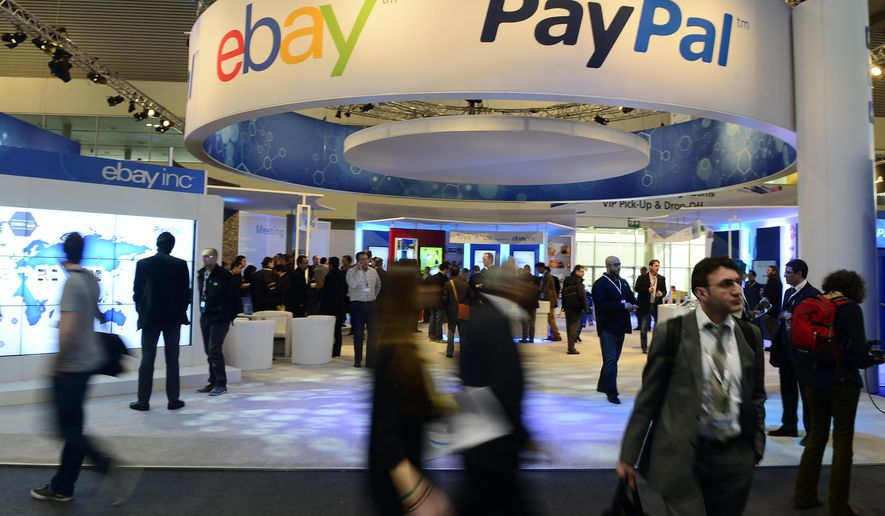 FILE - In this Wednesday, Feb. 27, 2013, file photo, attendees walk in front of an EBay and PayPal display area at the Mobile World Congress, the world's largest mobile phone trade show, in Barcelona, Spain. PayPal is splitting from EBay Inc. and will become a separate and publicly traded company during the second half of 2015. (AP Photo/Manu Fernandez, File)
