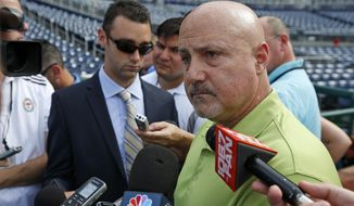 "FILE - In this July 31, 2014 file photo, Washington Nationals general manager Mike Rizzo pauses while speaking to reporters before a baseball game against the Philadelphia Phillies at Nationals Park in Washington. Two years after famously being shut down by the Washington Nationals to protect his elbow, Stephen Strasburg finally will make his postseason debut this week for the NL East champions. ""It's worked as planned,"" says Nationals general manager Mike Rizzo, the man responsible for holding out Strasburg in 2012. (AP Photo/Alex Brandon) ** FILE **"