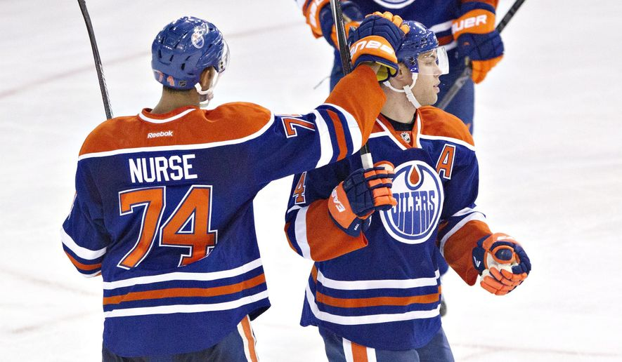 Edmonton Oilers Darnell Nurse (74) and Taylor Hall (4) celebrate a goal against the Winnipeg Jets during second period NHL hockey action in Edmonton, Alberta, on Monday, Sept. 29, 2014.(AP Photo/The Canadian Press, Jason Franson)