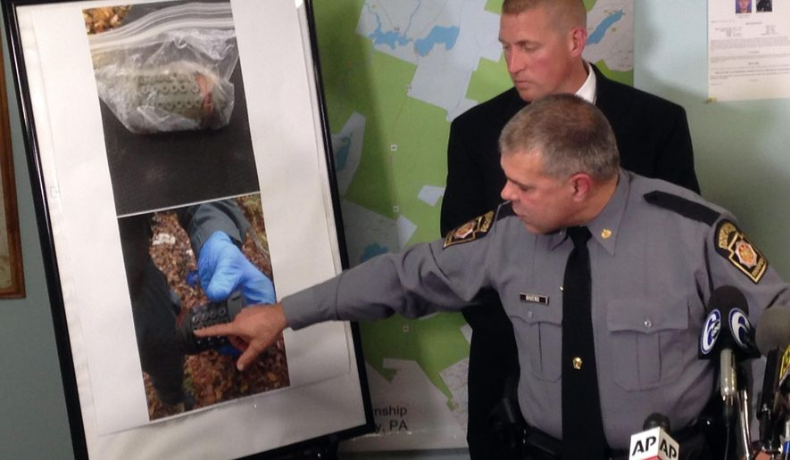 Lt. Col. George Bivens points to images of the pipe bombs that police say were left by trooper ambush suspect Eric Frein in the Pennsylvania woods, at a news conference in Blooming Grove Pa., Tuesday Sept. 30, 2014.  The bombs were not deployed, but they were fully functional and could have been set off by either a trip wire or a fuse, Bivens said. In background is John Brosnan, assistant special agent in charge of the FBI's Philadelphia office. (AP Photo/Michael Rubinkam)