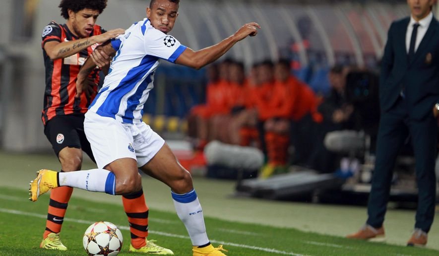 Porto's Cristian Tello, second left, is challenged by FC Shakhtar Donetsk's Taison during the Champions League Group H soccer match in Lviv, Ukraine, Tuesday, Sept. 30, 2014. (AP Photo/Yevheniy Kravs)