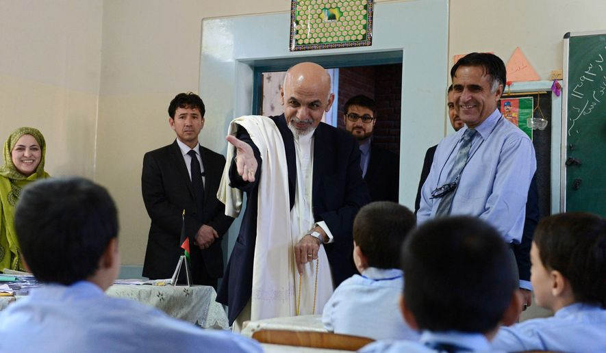 Afghan President Ashraf Ghani Ahmadzai, center, interacts with students during his visit to the Amani High School in Kabul on Tuesday,  Sept. 30, 2014. Afghanistan swore in Ghani Ahmadzai as its second elected president on Monday, embarking on a new era with a national unity government poised to confront a resilient Taliban insurgency by signing an agreement with the United States that would guarantee a continuing American military presence. (AP Photo/Wakil Kohsar, Pool)