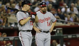 Washington Nationals' Stephen Strasburg, left, talks with third base coach Bob Henley (14) Arizona Diamondbacks during a baseball game on Tuesday, May 13, 2014, in Phoenix. (AP Photo/Matt York)