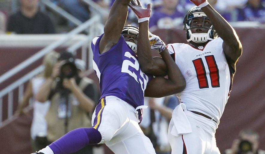 Minnesota Vikings cornerback Xavier Rhodes, left, breaks up a pass intended for Atlanta Falcons wide receiver Julio Jones (11) during the second half of an NFL football game, Sunday, Sept. 28, 2014, in Minneapolis. (AP Photo/Ann Heisenfelt)