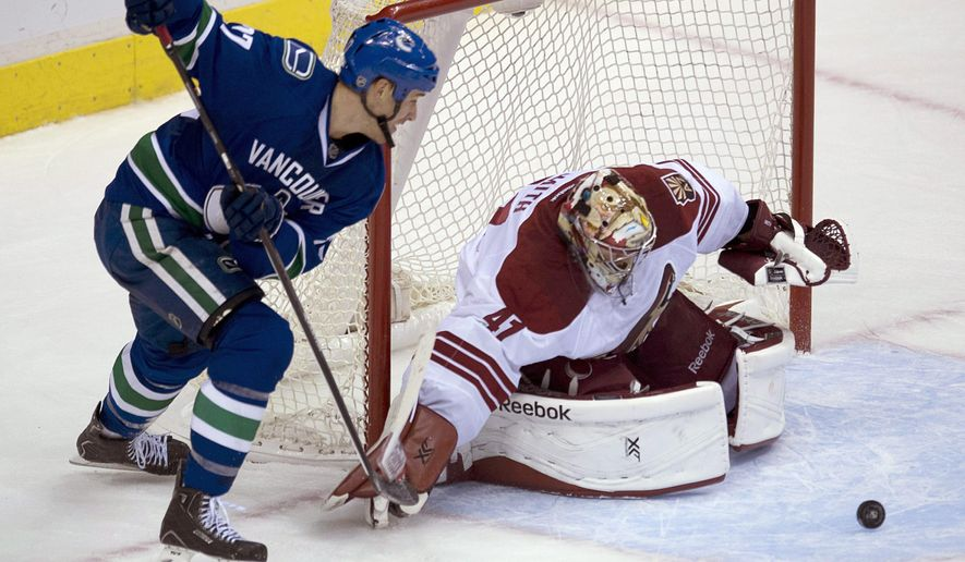 Vancouver Canucks center Shawn Matthias (27) tries to get a shot past Arizona Coyotes goalie Mike Smith (41) during the first period of an NHL hockey game in Vancouver, British Columbia, Monday, Sept. 29, 2014. (AP Photo/The Canadian Press, Jonathan Hayward)