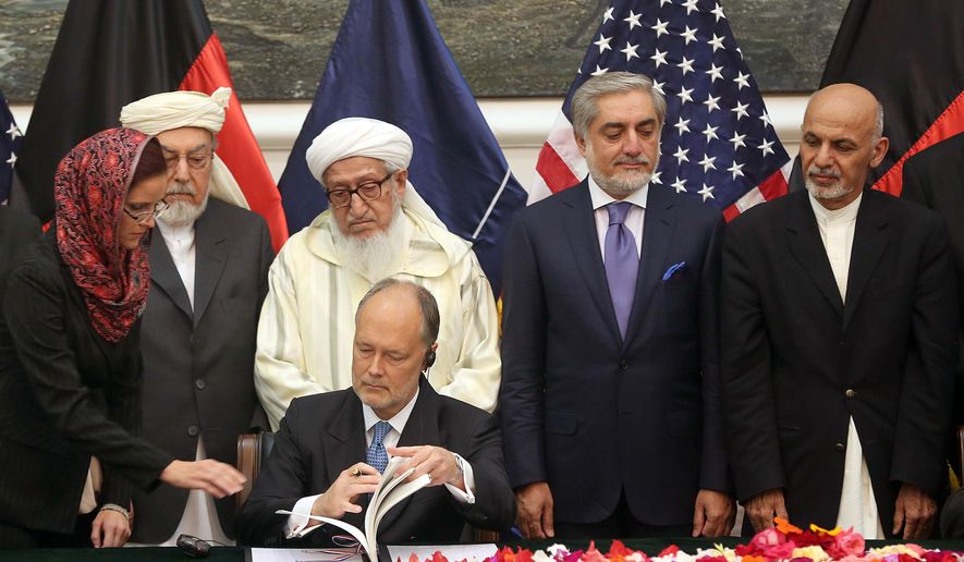 U.S. Ambassador to James Cunningham, seated, signs the documents of the Bilateral Security Agreement (BSA) at the presidential palace as Afghanistan's president Ashraf Ghani Ahmadzai, first right, and chief executive Abdullah Abdullah, second right, watch, in Kabul, Afghanistan, Tuesday, Sept. 30, 2014. Afghanistan and the United States signed a long-awaited security pact on Tuesday that will allow U.S. forces to remain in the country past the end of year. (AP Photo/Massoud Hossaini)