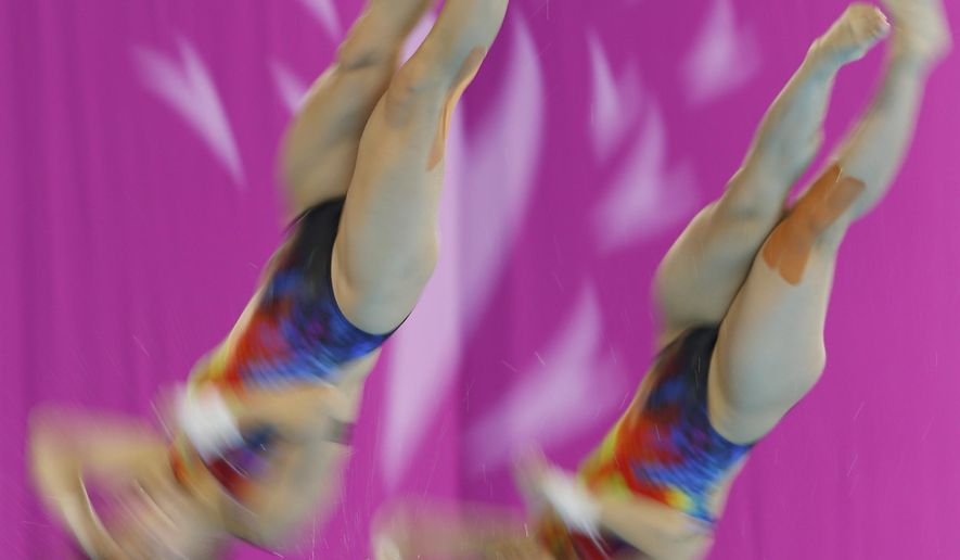 China's Chen Ruolin, left, and Liu Huixia compete during the women's synchronised 10m platform diving final at the 17th Asian Games in Incheon, South Korea, Tuesday, Sept. 30, 2014.  (AP Photo/Kin Cheung)