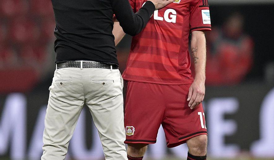 Leverkusen's head coach Roger Schmidt, left, touches Leverkusen's Stefan Kiessling after the German Bundesliga soccer match between Bayer Leverkusen and FC Augsburg in Leverkusen  Germany, Wednesday, Sept. 24, 2014. Leverkusen defeated Augsburg with 1-0. (AP Photo/Martin Meissner)
