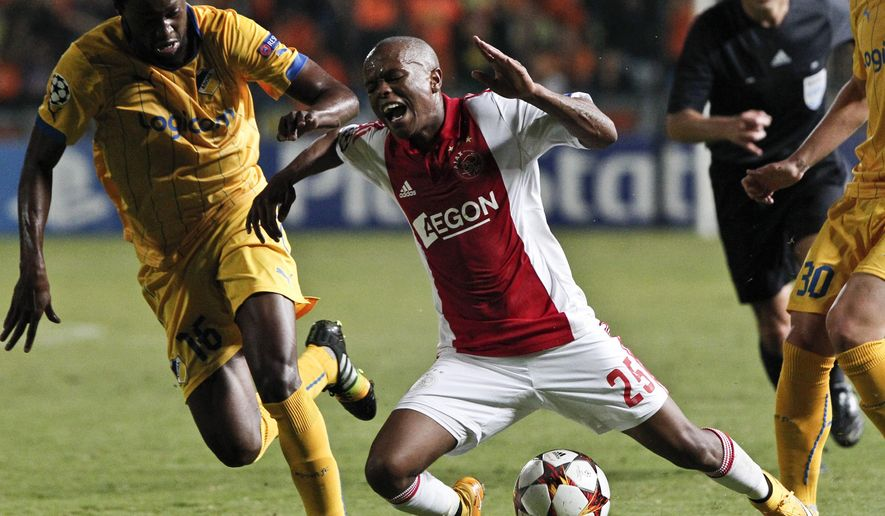 Apoel's Nicosia Vinicius, left, tries to stop Ajax's Thulani Serero during the Champions League Group F soccer match between Apoel and Ajax, at GSP stadium, Nicosia, Tuesday, Sept. 30, 2014. (AP Photo/Petros Karadjias)