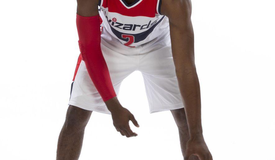 Washington Wizards guard John Wall (2) poses for photographs during NBA basketball media day at the Verizon Center in Washington, Monday, Sept. 29, 2014. (AP Photo/Carolyn Kaster)