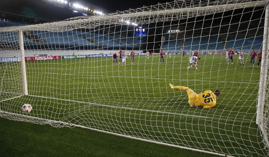 Bayern's Thomas Mueller scores 1-0 out of a penalty as CSKA's goalkeeper Igor Akinfeev dives to the wrong corner during the Group E Champions League match between CSKA Moscow and Bayern Munich at Arena Khimki stadium in Moscow, Russia, Tuesday Sept. 30, 2014. (AP Photo/Pavel Golovkin)