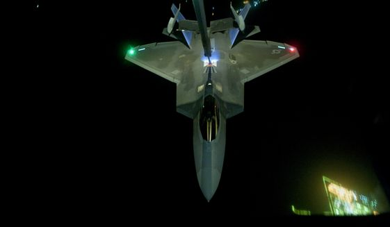 In this Friday, Sept. 26, 2014 photo, released by the U.S. Air Force, a U.S Air Force KC-10 Extender refuels an F-22 Raptor fighter aircraft prior to strike operations in Syria. These aircraft were part of a strike package that was engaging Islamic State group targets in Syria. Washington and its Arab allies opened the air assault against the extremist group on Sept. 23, striking military facilities, training camps, heavy weapons and oil installations. The campaign expands upon the airstrikes the United States has been conducting against the militants in Iraq since early August. (AP Photo/U.S. Air Force, Russ Scalf )
