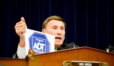 Rep. John Mica (R-Fla.) holds up a sign for the home security system company ADT during questioning towards Secret Service Director Julia Pierson as she testifies in front of the House Oversight and Government Reform Committee on Capitol Hill to discuss the recent White House perimeter breach when an armed Texas man made it into the White House earlier this month, Washington, D.C., Tuesday, September 30, 2014. (Andrew Harnik/The Washington Times)