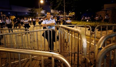 A local policeman stands guard behind barricades at the entrance of the government complex where Hong Kong Chief Executive Leung Chun-Ying's office is located. Student leaders of pro-democracy protests in Hong Kong warned Wednesday that if the territory's leader doesn't step down by the end of Thursday, they will step up their actions. (Associated Press)