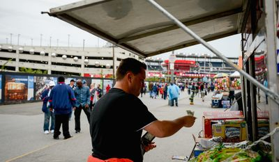 Daniel Flaherty of Arlington buys food from a street vendor before a Nationals game. deep postseason run scenario, according to D.C. Chamber of Commerce President and CEO Harry Wingo, could mean big bucks for some of his members. (Andrew Harnik/The Washington Times)