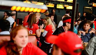 RED IS THE NEW GREEN: Katie Baucom (right) and Cate Scobel of the District visit Bluejacket Brewery before a Nationals game. Local businesses hope to stay bustling as the team brings in sold-out crowds during the playoffs. (Andrew Harnik/The Washington Times)