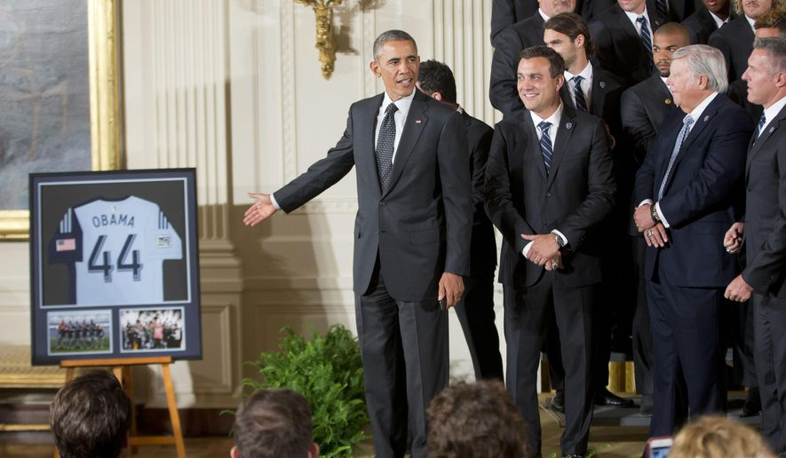 President Barack Obama points to a framed team jersey that was given to him by the members of the Sporting Kansas City soccer team during a ceremony in the East Room of the White House in Washington, Wednesday, Oct. 1, 2014, where he honored the 2013 Major League Soccer champions. (AP Photo/Pablo Martinez Monsivais)