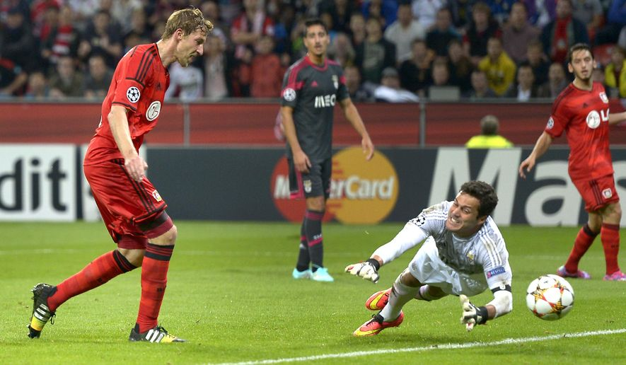 CORRECTS MONTH - Leverkusen's Stefan Kiessling, left, scores his side's first goal during the Champions League group C soccer match between Bayer 04 Leverkusen and SL Benfica at the BayArena stadium in Leverkusen, Germany, Wednesday, Oct. 1, 2014. (AP Photo/Martin Meissner)