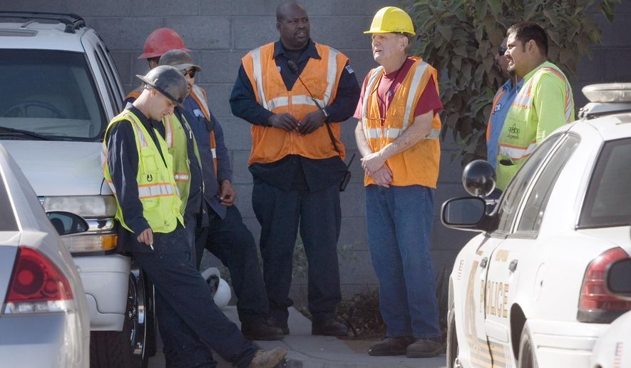 Advance Disposal workers wait outside of the company's facility Wednesday, Oct. 1, 2014, in Hesperia, Calif., as San Bernardino County Sheriff's deputies and detectives begin an investigation after a body of an infant was found in the trash and recycling sorting facility. (AP Photo/The Victor Valley Daily Press, James Quigg)
