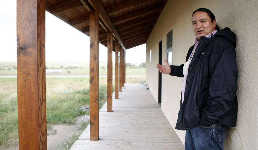 In this photo taken on Tuesday, Sept. 30, 2014, Nick Tilsen, executive director for the Thunder Valley Community Development Corporation, shows the front porch of the first home under construction at the Thunder Valley community on the Pine Ridge Indian Reservation in Pine Ridge, S.D. The house is part of the planned community vying for the $100,000 grand prize in the Buckminster Fuller Institute Challenge. (AP Photo/Rapid City Journal, Sean Ryan) TV OUT (REV-SHARE)